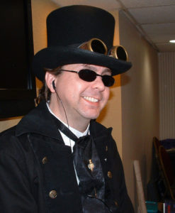 Author Mike Stewart in a top hat and goggles smiling as he runs a session of the Victorious RPG