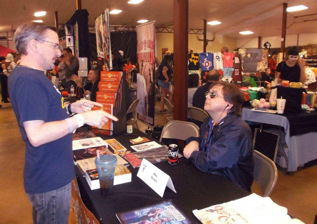 Author Mike Stewart sitting at table speaking with convention attendees.