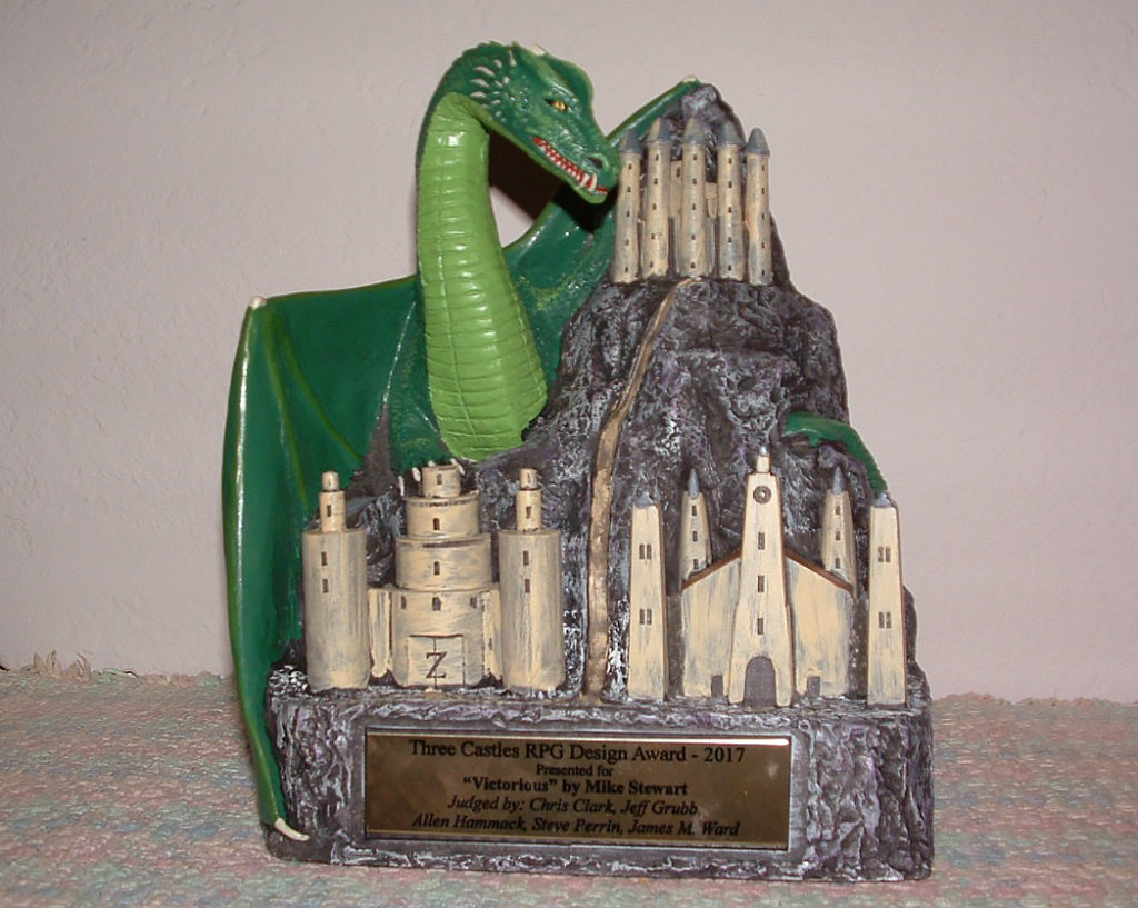 "A small statue of a green dragon looming over a rocky crag with three castles on it. The plaque below reads: ""Three Castles RPG Design Award - 2017. Presented to 'Victorious' by Mike Stewart. Judged by: Chris Clark, Jeff Grubb, Allen Hammack, Steve Perrin, James M. Ward"""